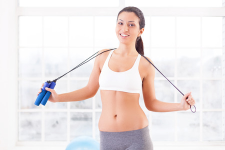 skipping: Sporty woman. Cheerful young sporty woman holding a jumping rope at her shoulders and looking at camera while standing in sport club
