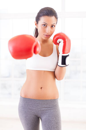 Woman punching. Confident young woman in boxing gloves stretching out her hand and looking at camera  photo