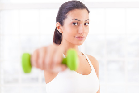 Woman exercising. Beautiful young Indian woman stretching out hand with dumbbell and looking at camera photo