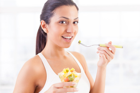 This is my favorite food. Side view of beautiful young Indian woman eating a fruit salad and smiling photo