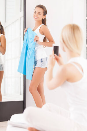 Thins color fits you best. Beautiful young woman standing near the mirror with blue dress in hands and looking at her friend sitting on the foreground with mobile phone photo