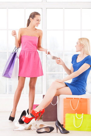 Try this shoes. Two attractive young women choosing shoes in a shoe store photo