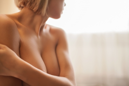 Naked beauty. Cropped image of beautiful young shirtless woman covering breast with hands