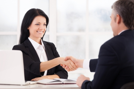 Sealing a deal. Two cheerful business people handshaking and smiling while sitting face to face at the table photo