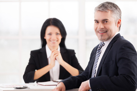 I got this job. Cheerful mature man in formal wear smiling at camera while woman in suit sitting photo