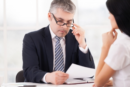 Checking a report. Thoughtful grey hair man in formalwear looking at the paper and adjusting glasses while woman sitting in front of him and holding hand on chin photo