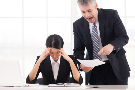 You are doing it all wrong! Furious mature businessman holding document and shouting while depressed woman sitting at the table and holding head in hands photo