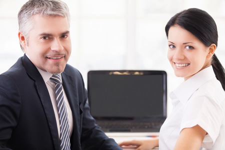Working together. Cheerful man and woman in formalwear working on laptop and looking over shoulder photo