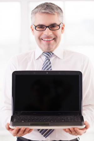 Your advertisement here. Smiling senior man in shirt and tie holding laptop and showing the monitor to you  photo