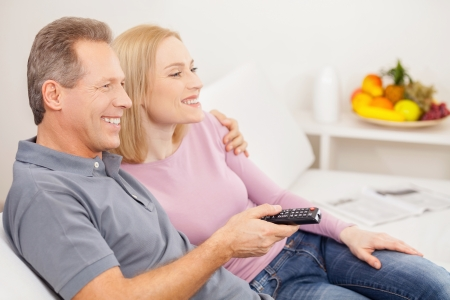 Watching TV together. Side view of cheerful mature couple sitting together and watching TV photo