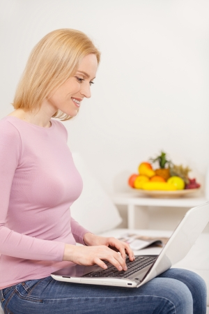 surfing the web: Surfing web at home. Side view cheerful blond hair woman using laptop and smiling