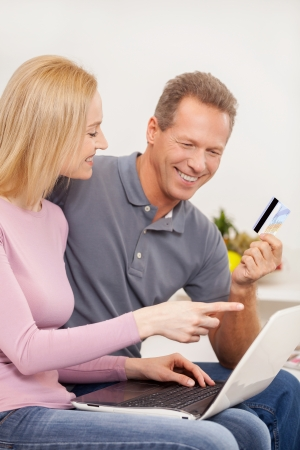 Online shopping. Side view cheerful mature couple using laptop together and smiling while man holding a credit card photo