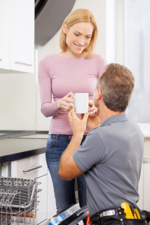 Coffee after hard work. Cheerful blond hair woman giving a cup of coffee to handyman photo