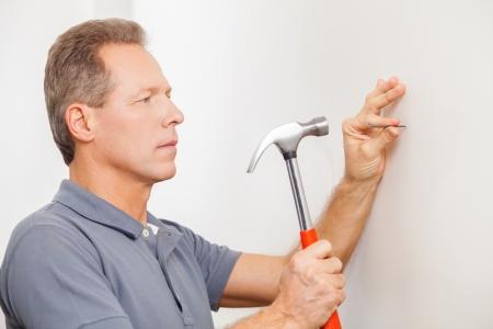 handcarves: Man hammering a nail. Confident mature grey hair man hammering a nail  Stock Photo