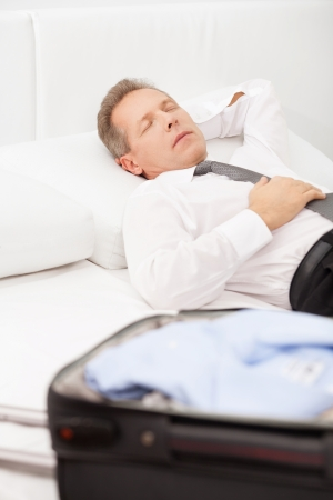 grey hair: Tired businessman sleeping. Tired grey hair man in shirt and tie lying on bed and keeping eyes closed while luggage laying on bed