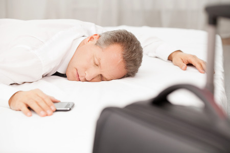 hotel bed: Tired and overworked. Tired grey hair man in shirt and tie sleeping on bed while luggage laying on foreground Stock Photo