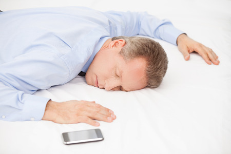 grey hair: Tired businessman. Top view of tired grey hair man in blue shirt sleeping on bed