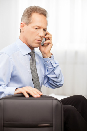 Confident executive. Serious grey hair man in shirt and tie talking on the phone while sitting on bed   photo
