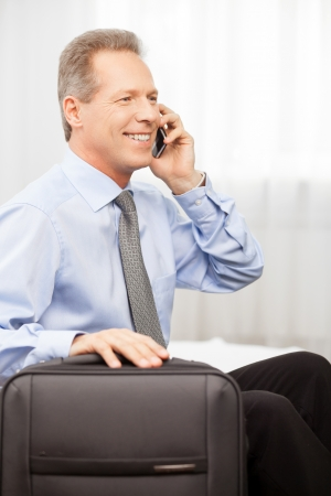 I am going home. Smiling grey hair man in shirt and tie talking on the phone while sitting on bed   photo