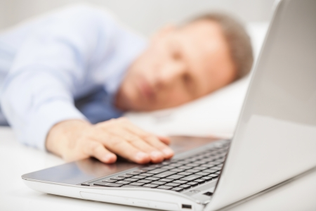 grey hair: Overworked businessman. Grey hair man in formalwear holding hand on laptop keyboard while sleeping in bed