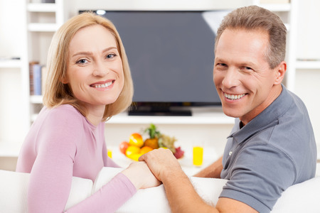 Happy mature couple. Cheerful mature couple sitting in front of TV and looking over shoulder photo
