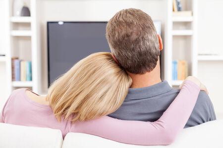 pareja viendo television: Pareja viendo la televisión. Vista trasera de una pareja madura que se sienta delante de la televisión, mientras que la mujer abrazando a su marido