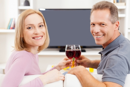 Happy to be together. Rear view of smiling mature couple sitting in front of TV and holding glasses with red wine  photo