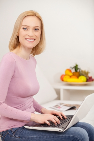 cheveux blonds: Faire des affaires � la maison. Vue de c�t� gai femme blonde utilisant un ordinateur portable et souriant � la cam�ra