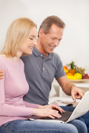 surfing the web: Surfing web together. Side view cheerful mature couple using laptop together and smiling