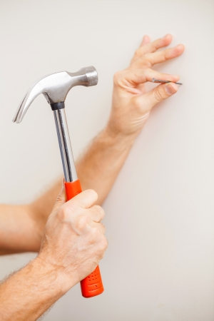 Hammering a nail. Close-up of man hammering a nail  photo