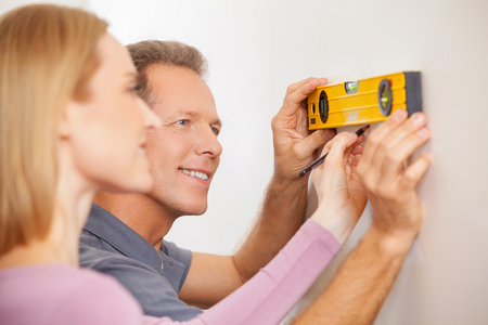 Couple measuring wall. Cheerful mature couple taking measurements of the wall and smiling photo