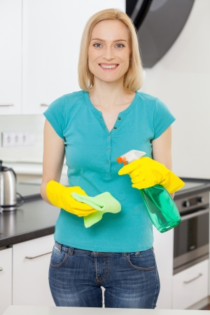 housewife gloves: Housewife at work. Mature blond hair woman in yellow gloves holding a rag and spray bottle while smiling at camera