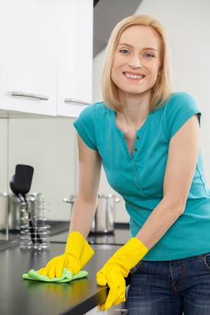housewife gloves: Housewife at work. Mature blond hair woman in yellow gloves polishing furniture and smiling at camera