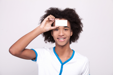 forehead: Copy space on my forehead. Cheerful African teenager holding plastic card at his forehead and looking at camera while standing isolated on grey  Stock Photo