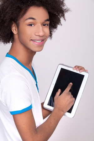 looking over shoulder: Working on digital tablet. Rear view of cheerful African teenager working on digital tablet and looking over shoulder while standing isolated on grey