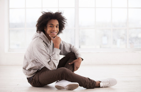 Carefree teenager. Teenage African boy sitting on the floor and holding hand on chin  Stock Photo - 25272296