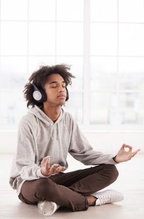 Chill time. Teenage African boy in headphones listening to the music and keeping eyes closed while sitting in lotus position on the floor