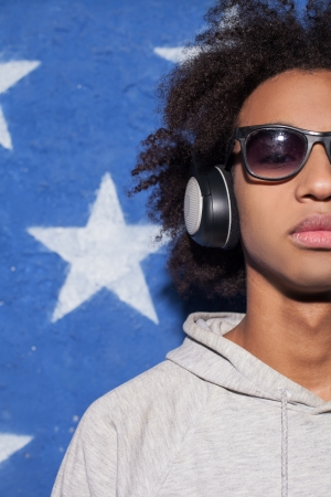 Music lover. Cropped image of confident young African man in\ headphones standing against American flag and listening to the\ music