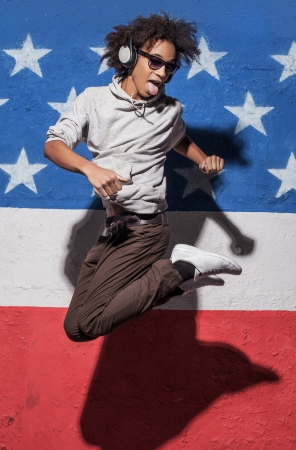 hands out: Jump! Cheerful young African man in headphones jumping against American flag Stock Photo