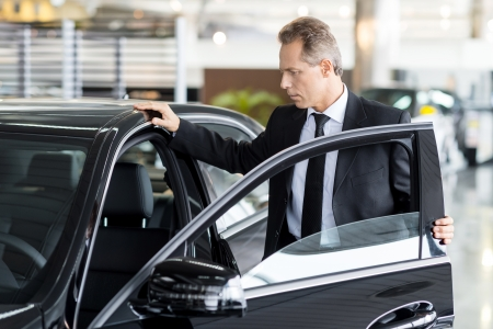 Examining his new car. Confident mature man in formalwear opening the car door at the dealership photo