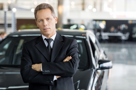 dealership: Confident in his choice. Mature grey hair man in formalwear standing in front of car and looking at camera Stock Photo