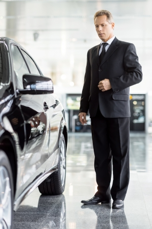 grey hair: Perfect car for me. Full length of mature grey hair businessman standing near car at the dealership 스톡 사진