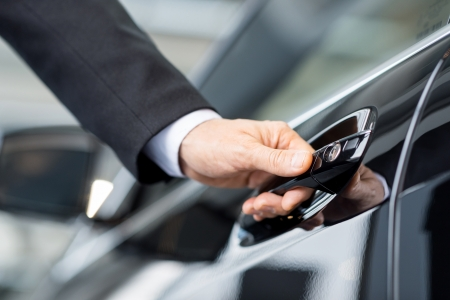 car sales: Opening his new car. Close-up of male hand holding the car handle