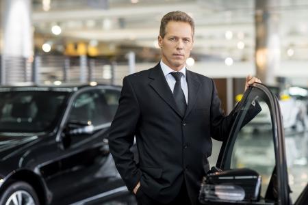 Vertrouwen in zijn keuze. Zelfverzekerd grijs haar man in formalwear houden hand op de geopende autodeur en kijken naar de camera