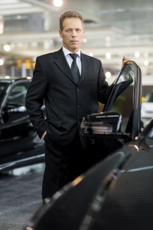 Ma voiture neuve. Confiant matures cheveux gris dans formalwear homme tenant la main sur la porte de la voiture ouverte et regardant la caméra