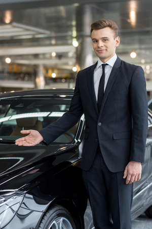 Let me present our best model. Handsome young car salesman standing at the dealership and pointing car photo