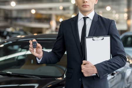 Key from your new car. Cropped image of young car salesman standing at the dealership and holding a key photo