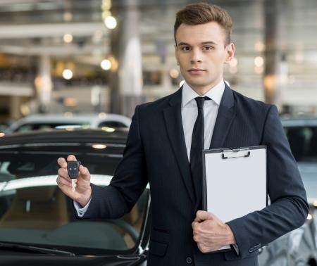 Klucze: Tu jest klucz! Przekonany, młody sprzedawca klasyczny samochód stoi w salonie i przytrzymanie klawisza