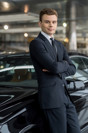 Confident in his choice. Confident man in formalwear leaning at the car and looking at camera while standing at car dealership Stock fotó