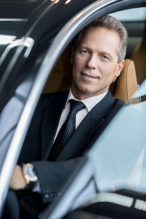 one senior man only: Business trip. Confident senior businessman sitting in car and smiling at camera
